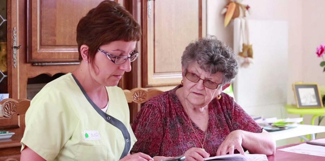 personne âgée avec aide à domicile assises à une table