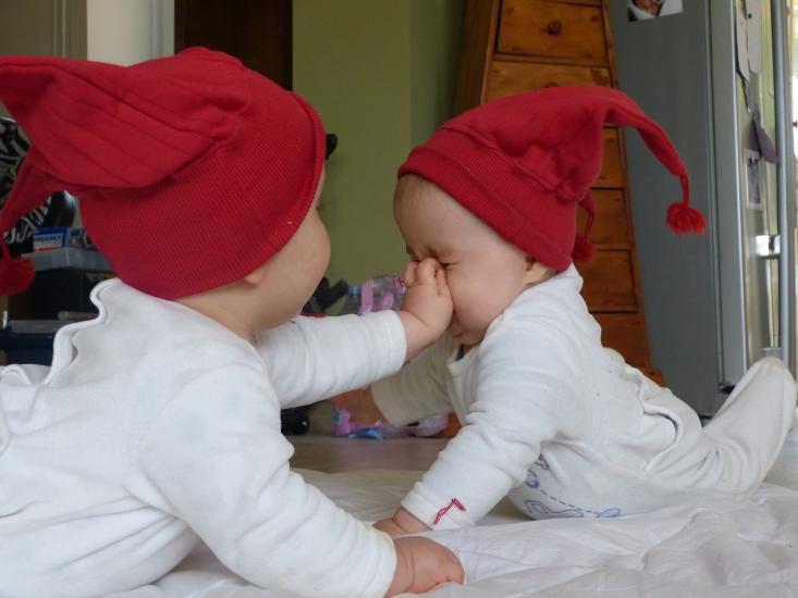 jumeaux avec bonnets rouges jouant au sol